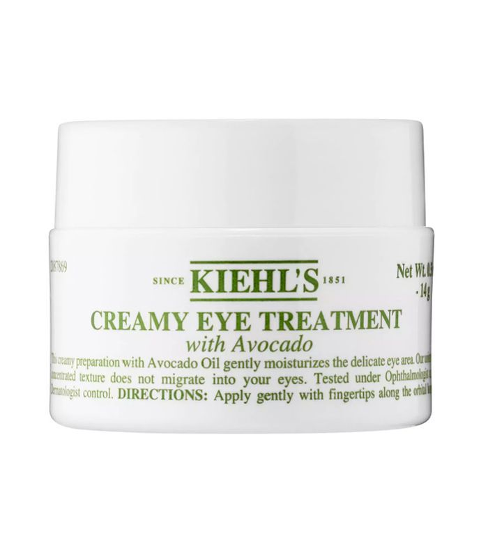 A small white pot of eye cream with green writing.