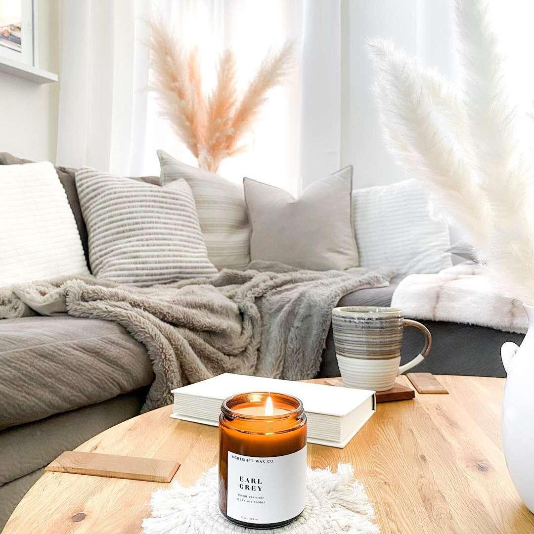 Cozy living room with lit candle and coffee mug.