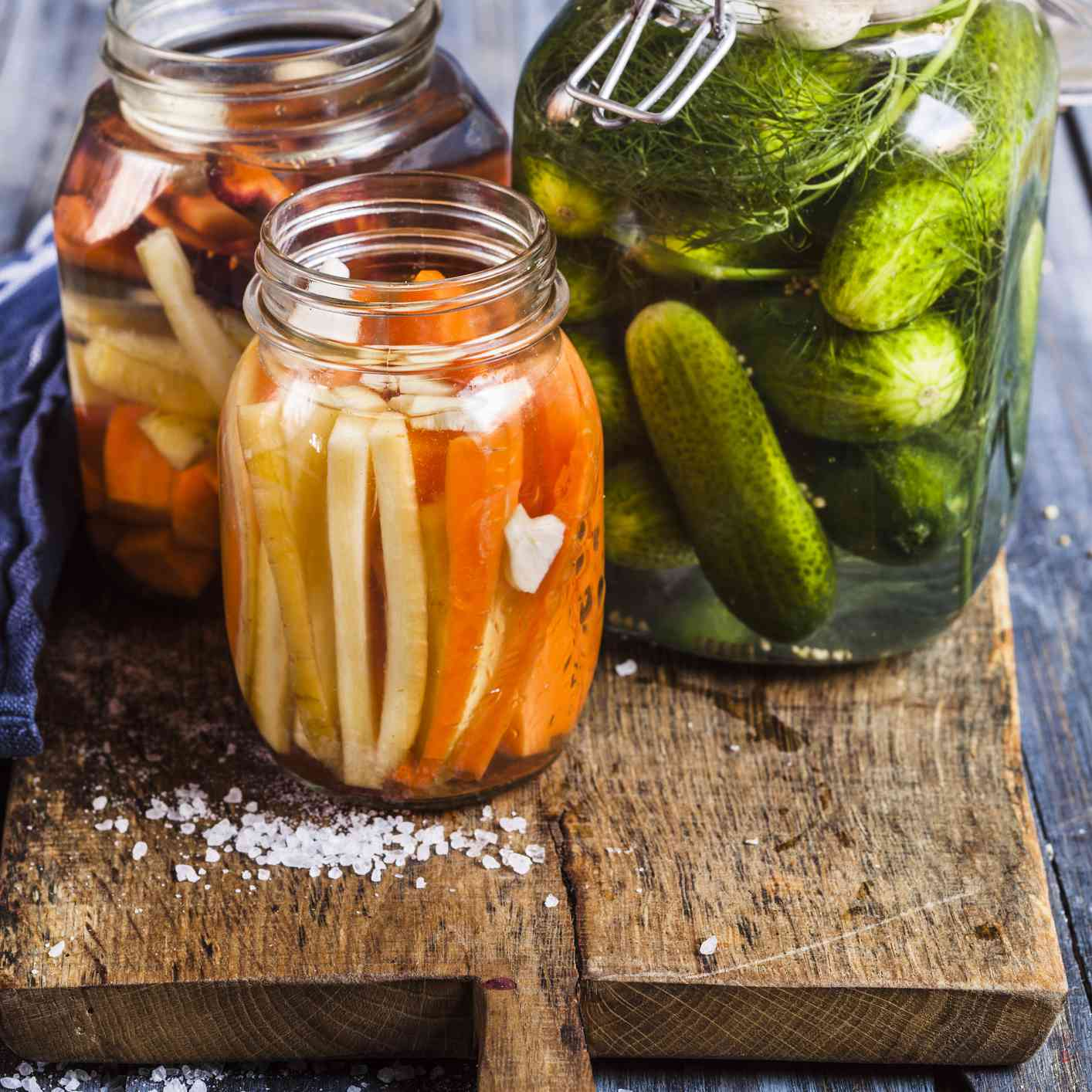 Fermented vegetables in glass jars on a wooden cutting board