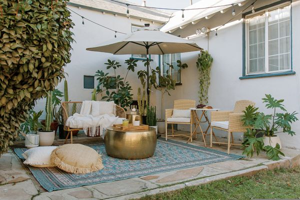 A patio with a blue rug.