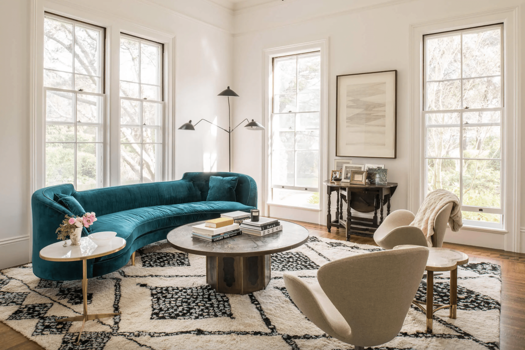 Soft living room with velvet couch and plush rug.
