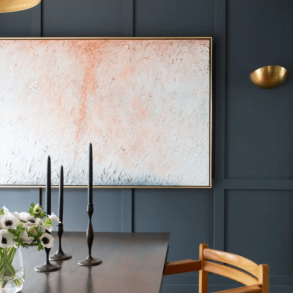 A dining room with a dark wooden table and even darker navy walls