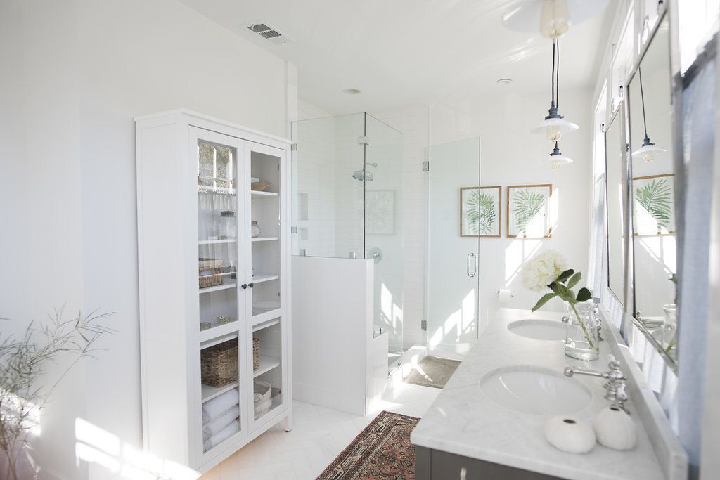 All-white bathroom with marble jack-and-jill sinks, patterned area rug
