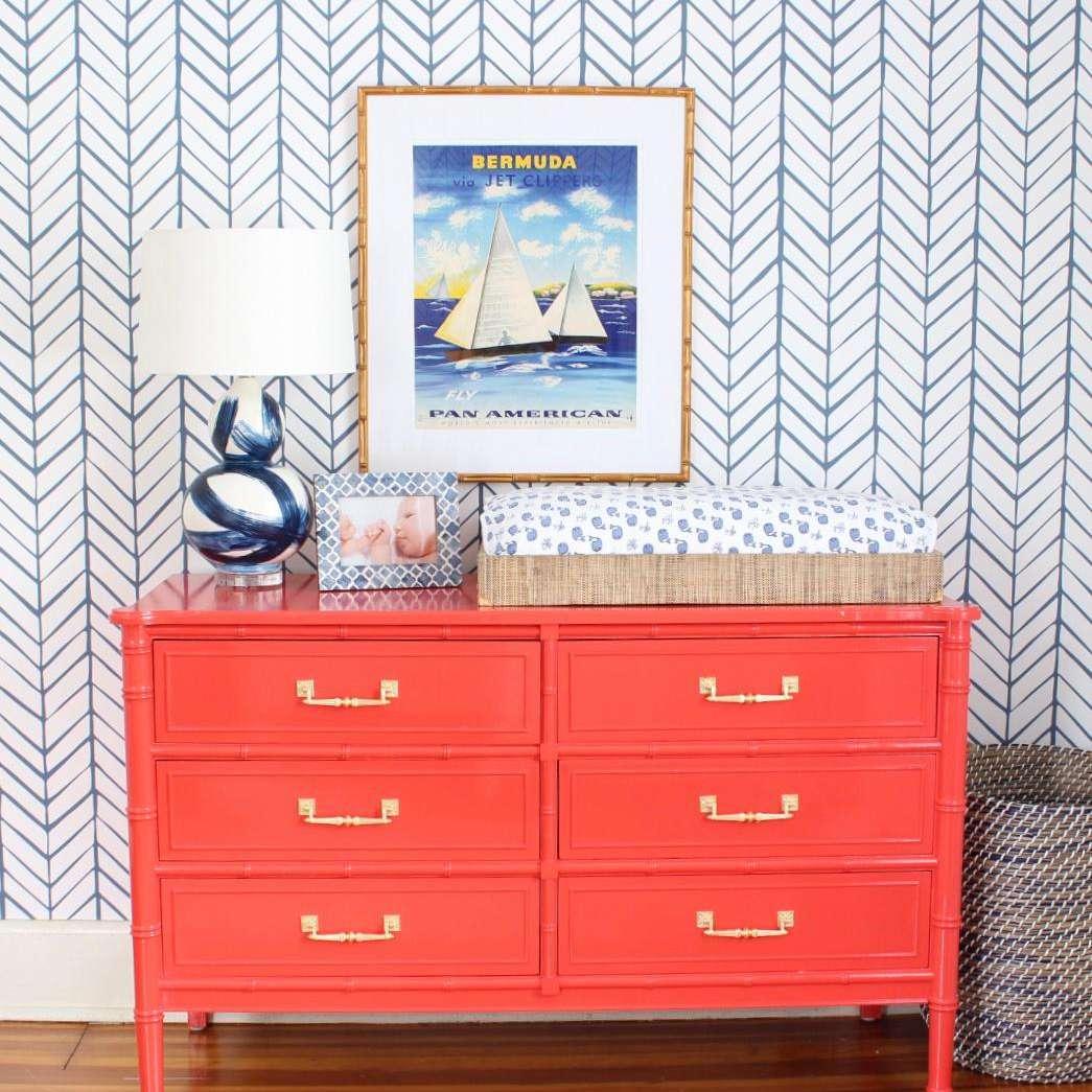 Bright orange dresser with vintage Bermuda poster hanging above.