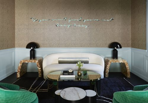 Luxe living room with neon Ricky Bobby quote above couch.