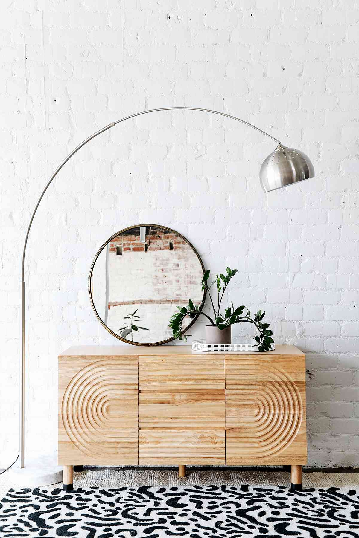 Modern vignette with wood architectural dresser, abstract rug, and simple styling