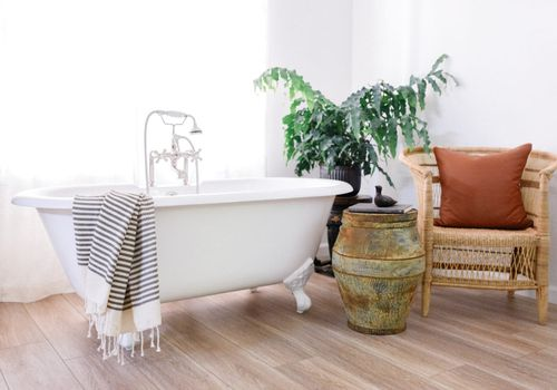 bathroom with rattan chair, plant, and freestanding tub