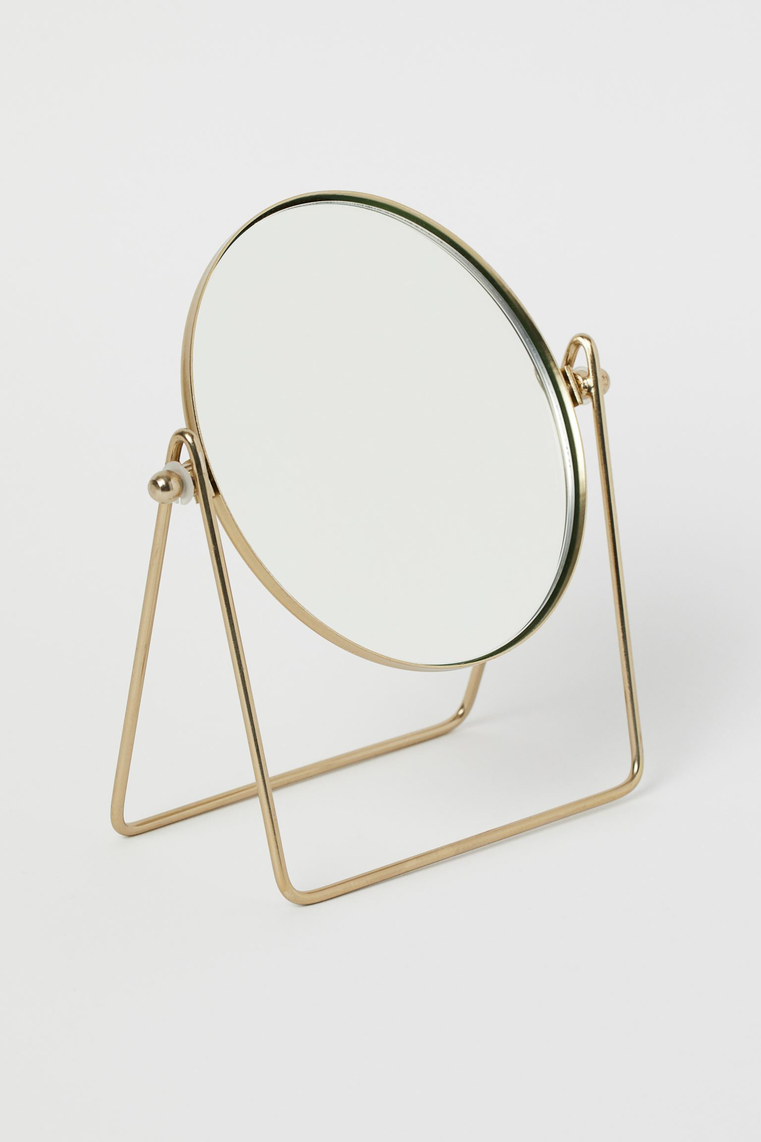 Metal table mirror in gold.
