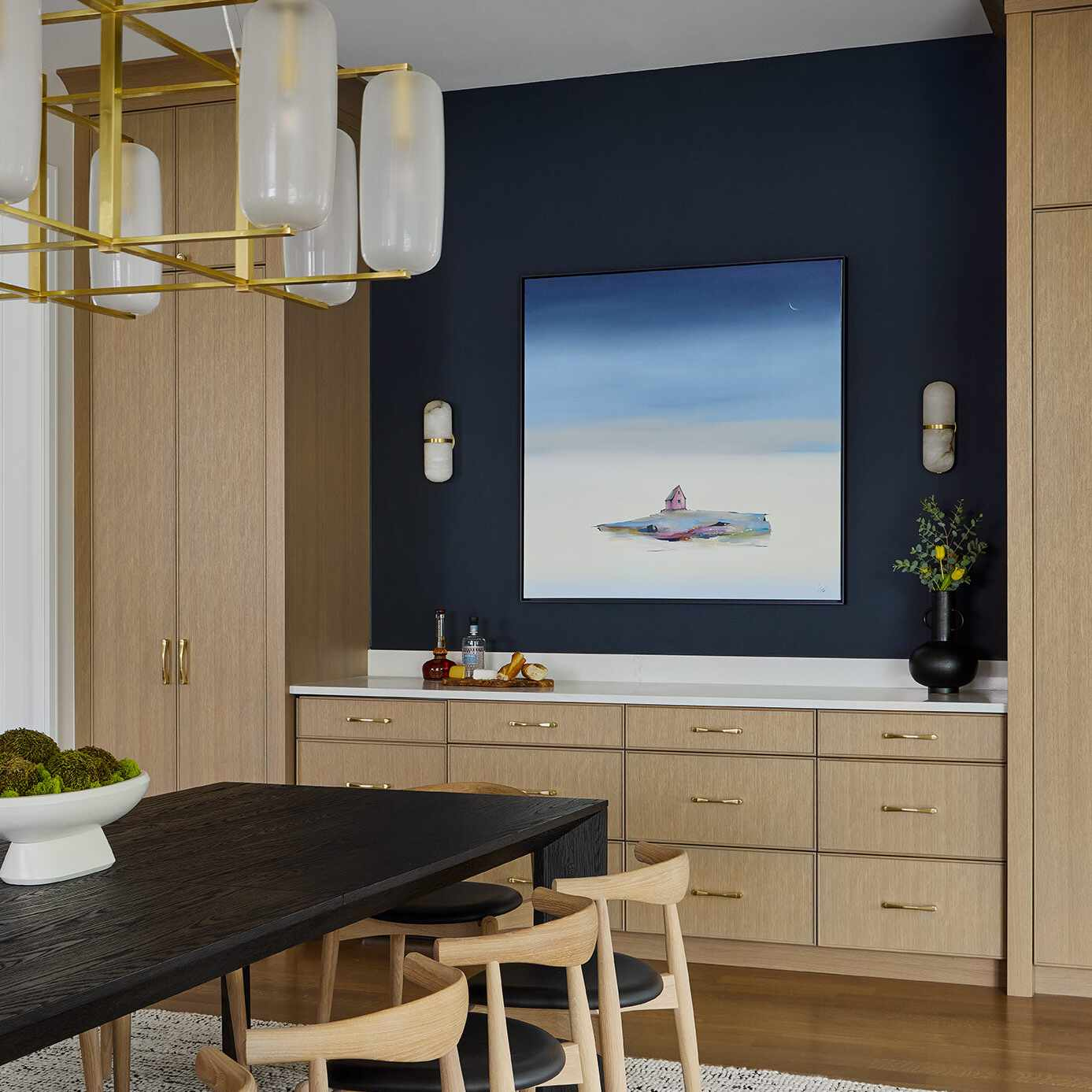 A dining room with one navy wall, which has been broken up with a lighter blue painting