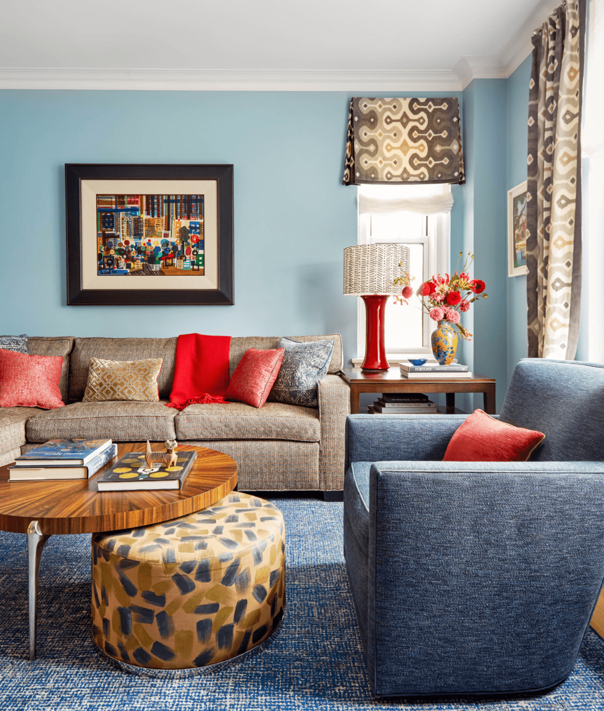 Blue living room with poppy colored accents.