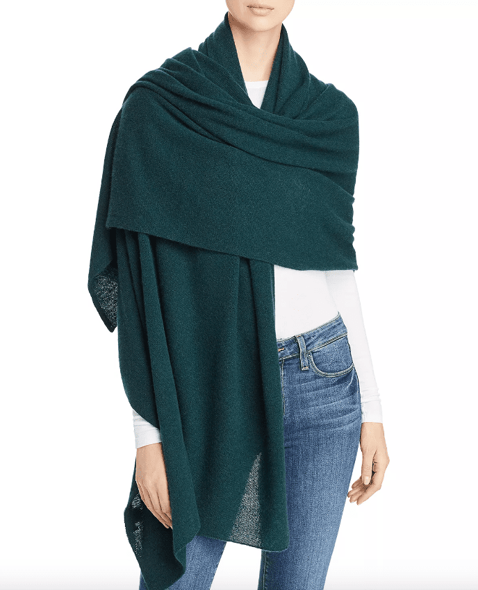 A green cashmere travel wrap, wrapped around a woman wearing jeans and a white longsleeve shirt.