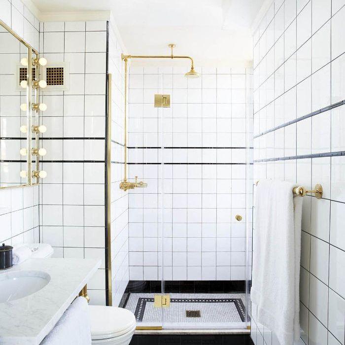 un baño negro, blanco y latón