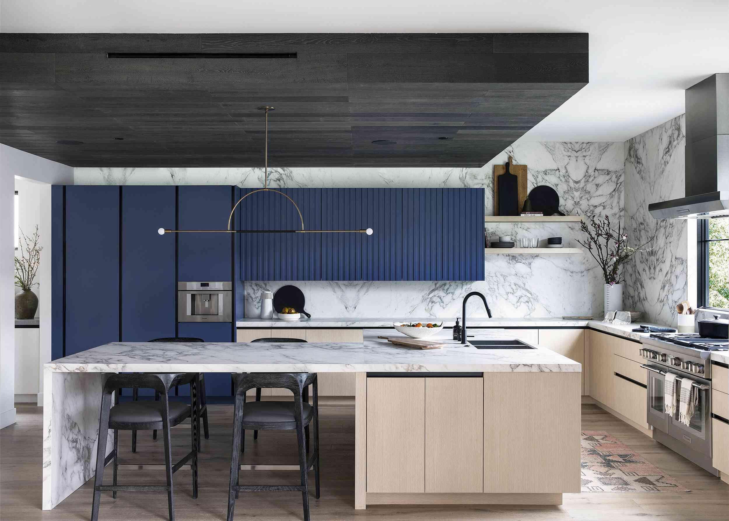 Sleek stone kitchen with minimal overhead light fixture