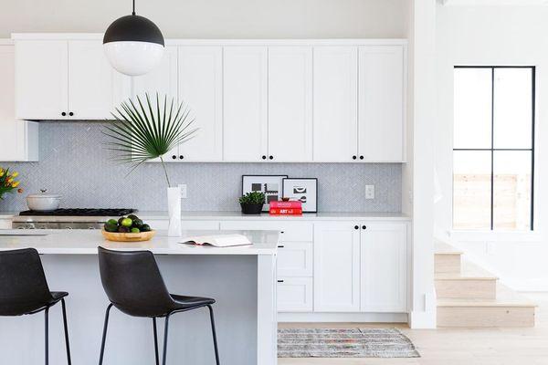Bright white kitchen with palm leaf decoration.