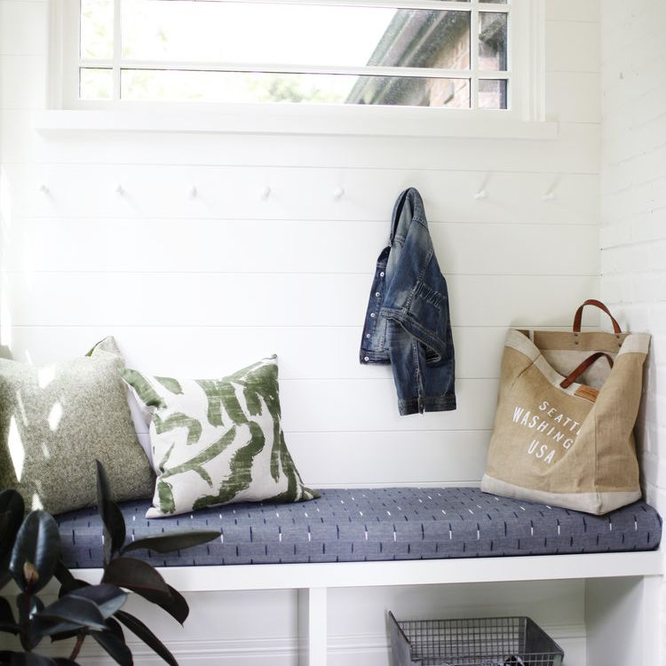 A small mudroom with several hooks and a bench
