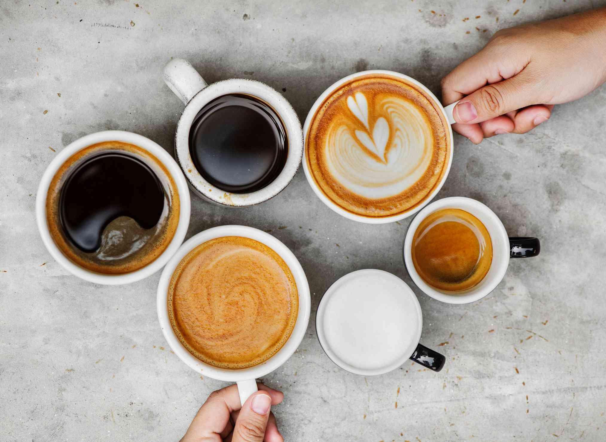 Un grupo de tazas llenas de café negro y lattes.