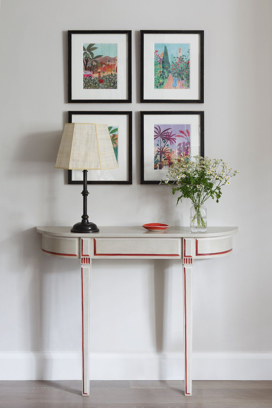 A gray wall with art and a decorative cabinet on it