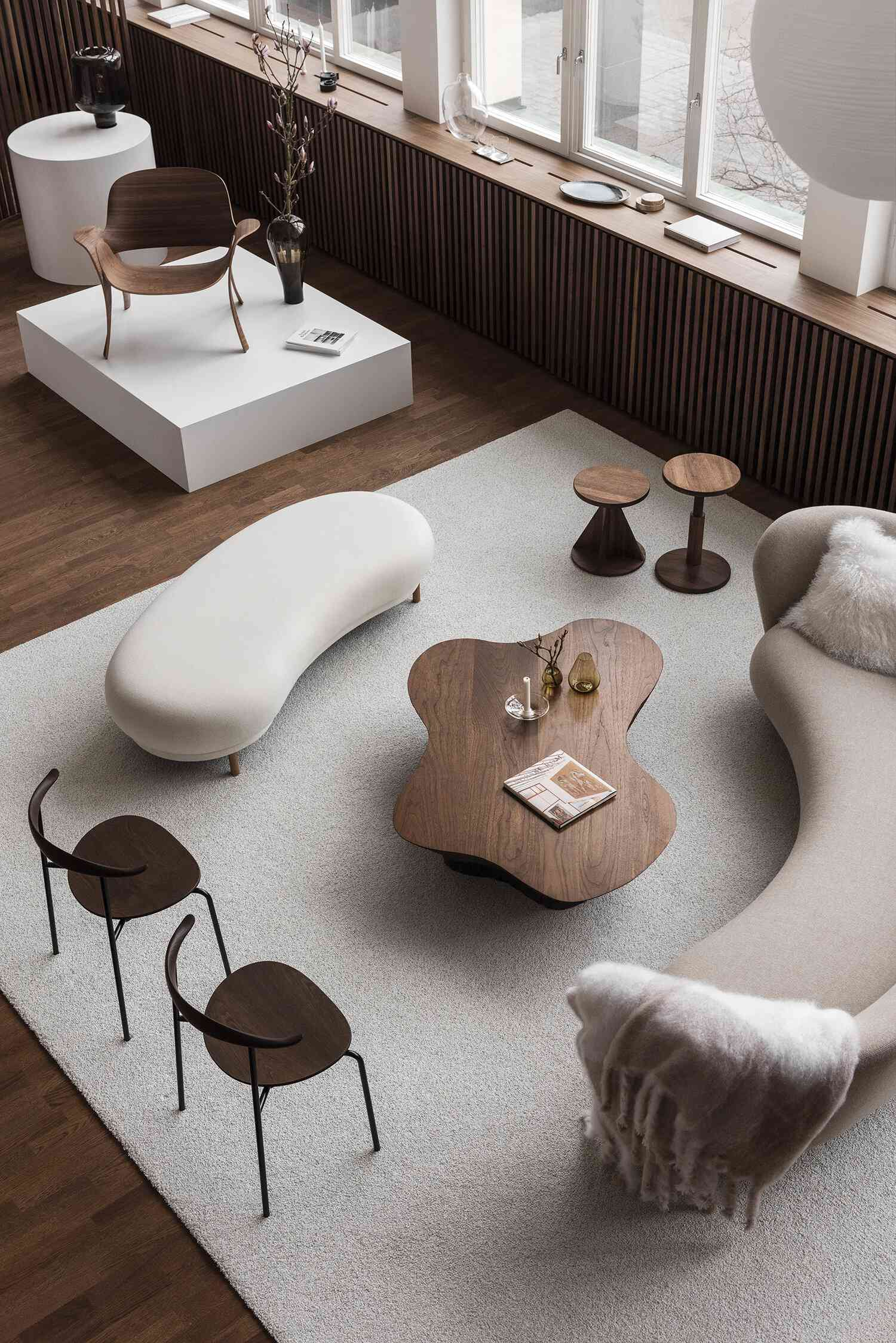 An overhead shot of a living room with contemporary curved couches and tables