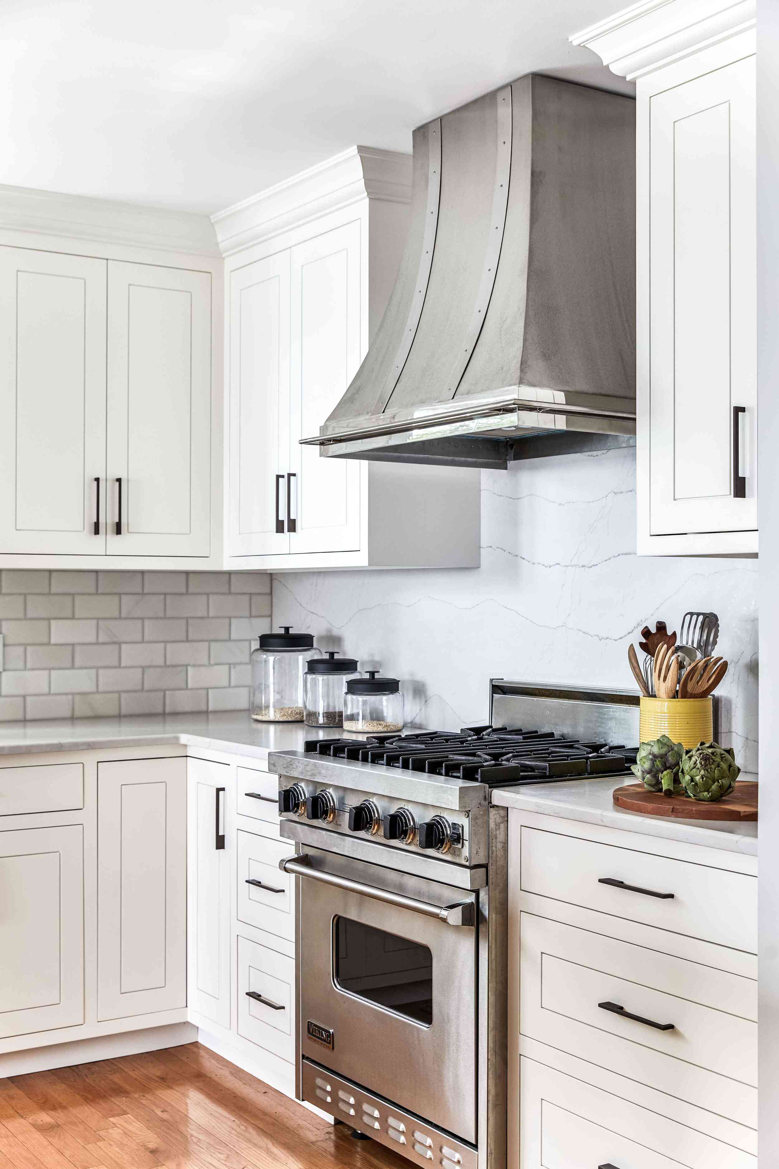 A kitchen with two white backsplashes: one crafted from tiles, and one crafted from marble