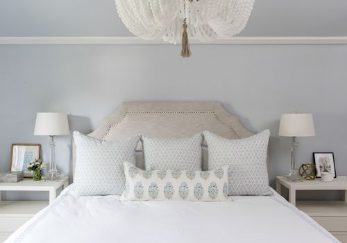 White bedding in soft blue bedroom.