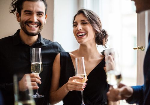 Happy man and woman holding champagne flutes during dinner party