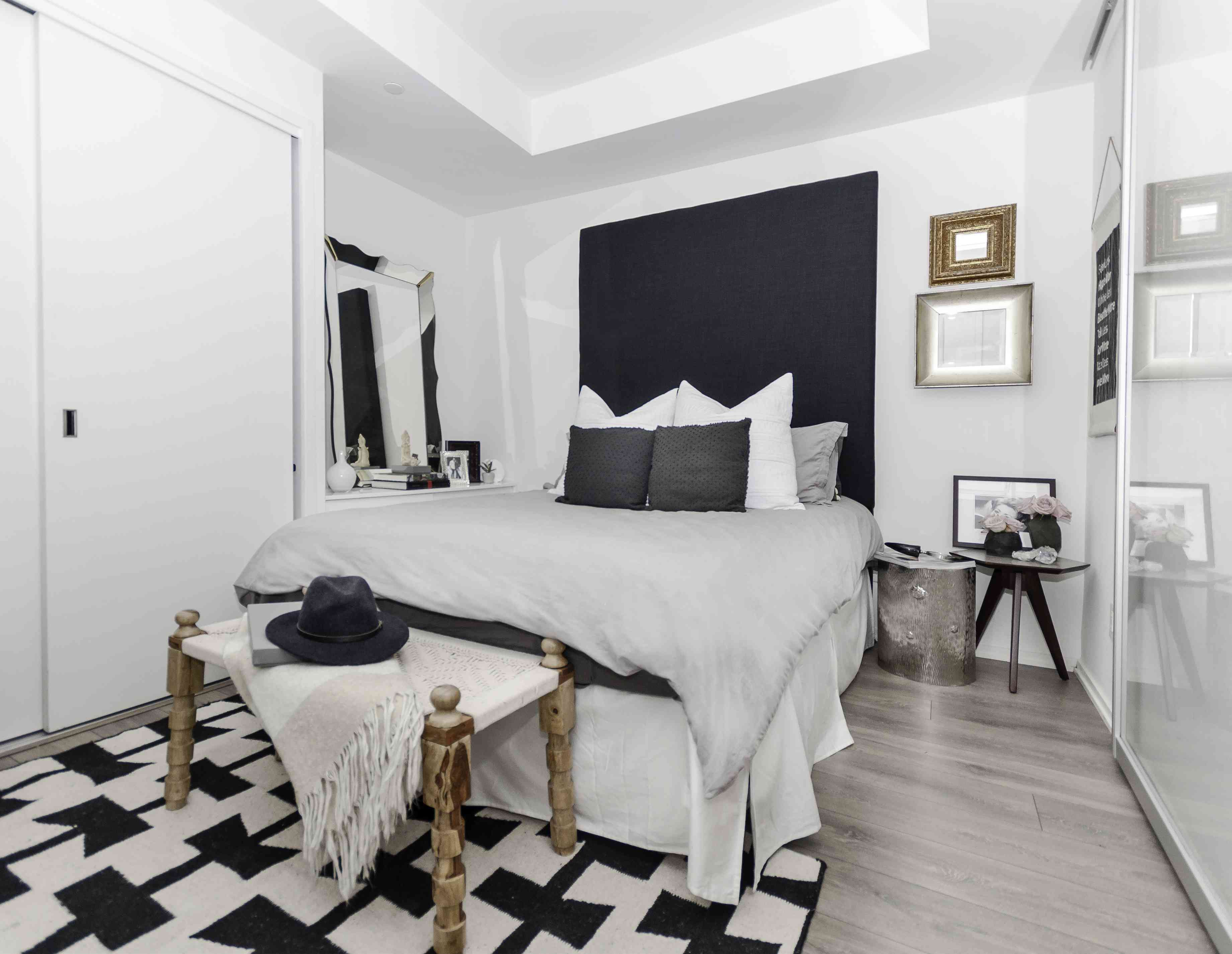 White and black bedroom with large black headboard.