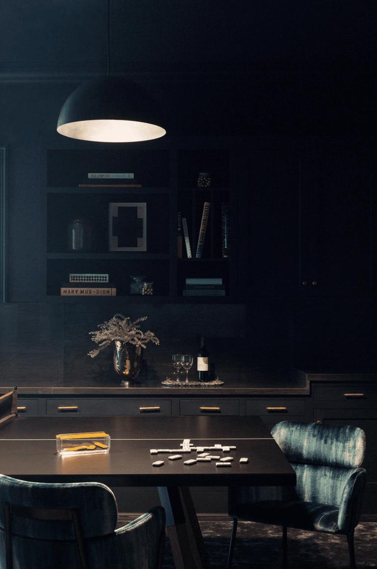 A hazy game room lit by a single pendant light
