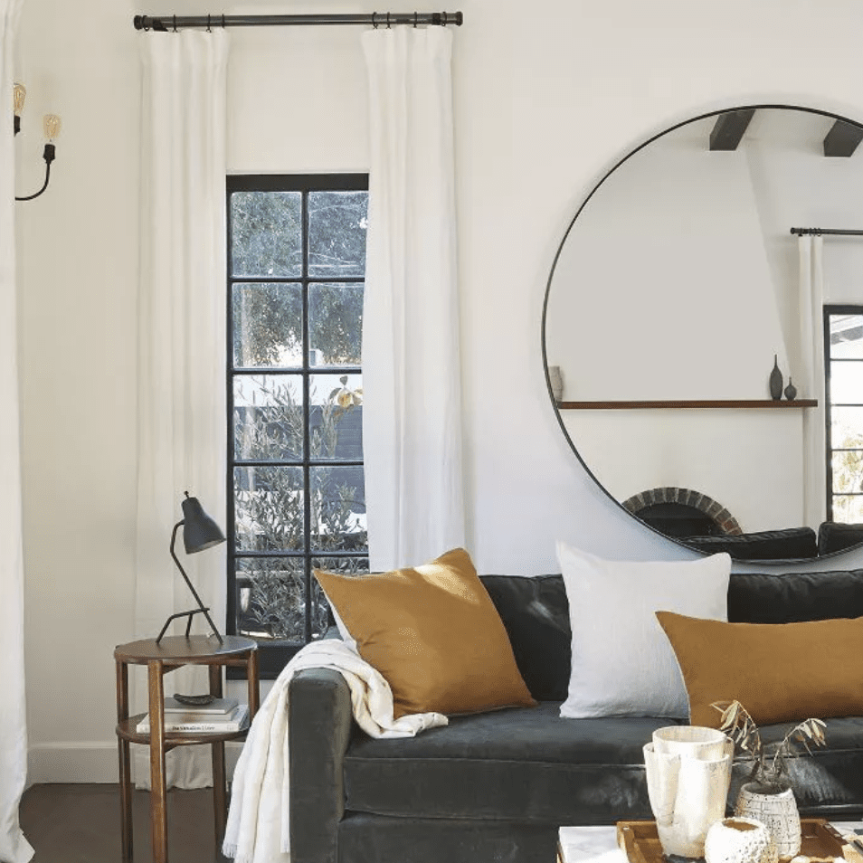 Braided wool rug by Parachute defines living room with dark couch, marble coffee table and large, hung round mirror