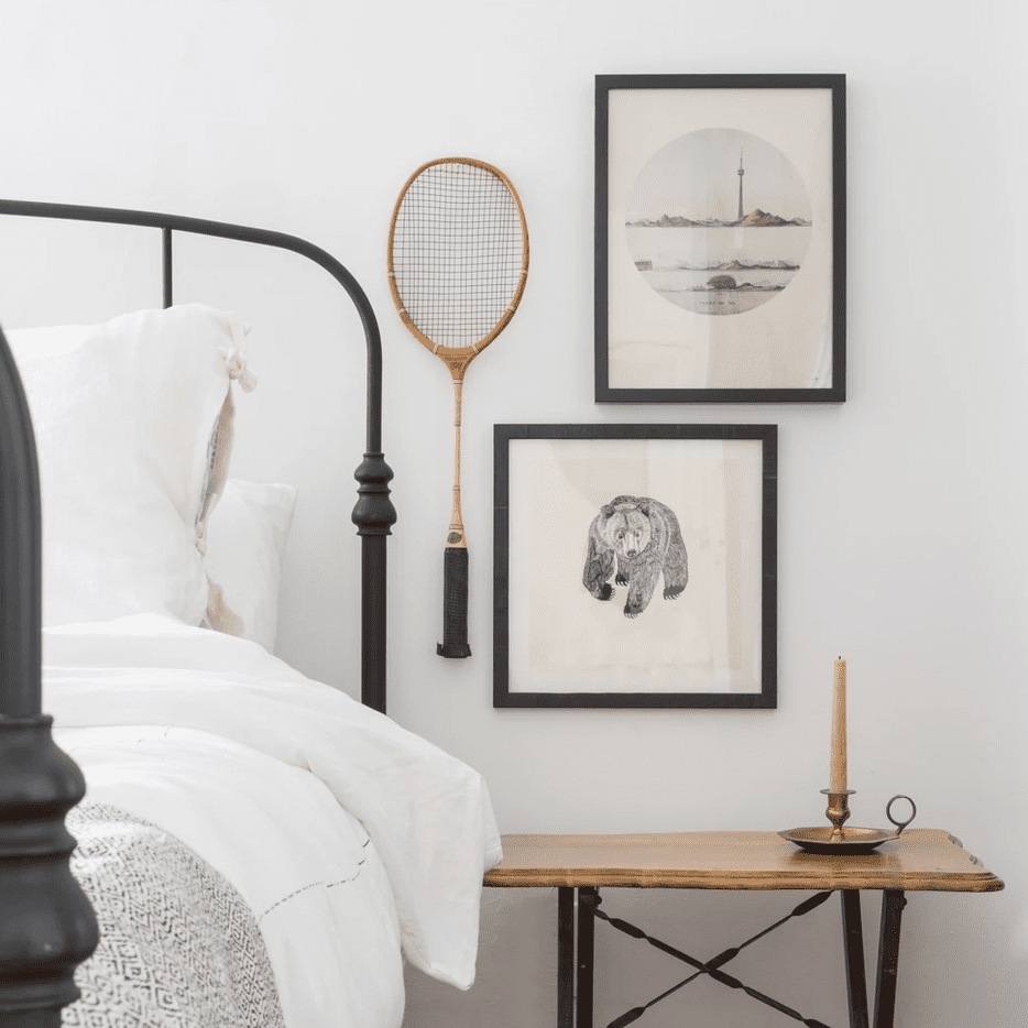 A small bedroom gallery wall, made up of two prints and a vintage badminton racquet