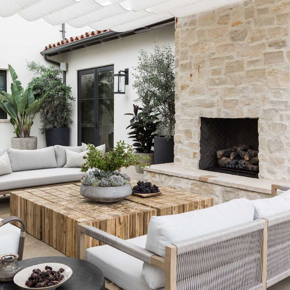 An outdoor patio, centered around a stone-lined outdoor fireplace