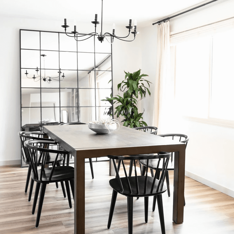 A dining room with a black chandelier, a matching black mirror, and matching black chairs