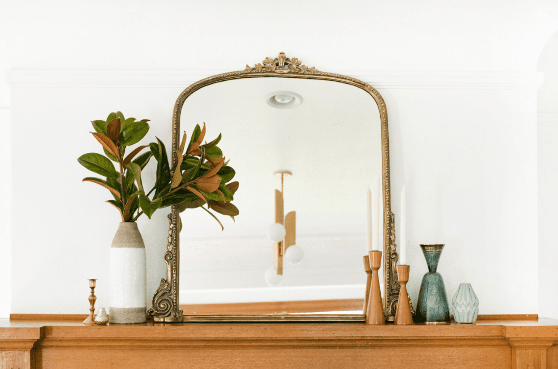 A mantle topped with a gold mirror and several smaller pieces of decor