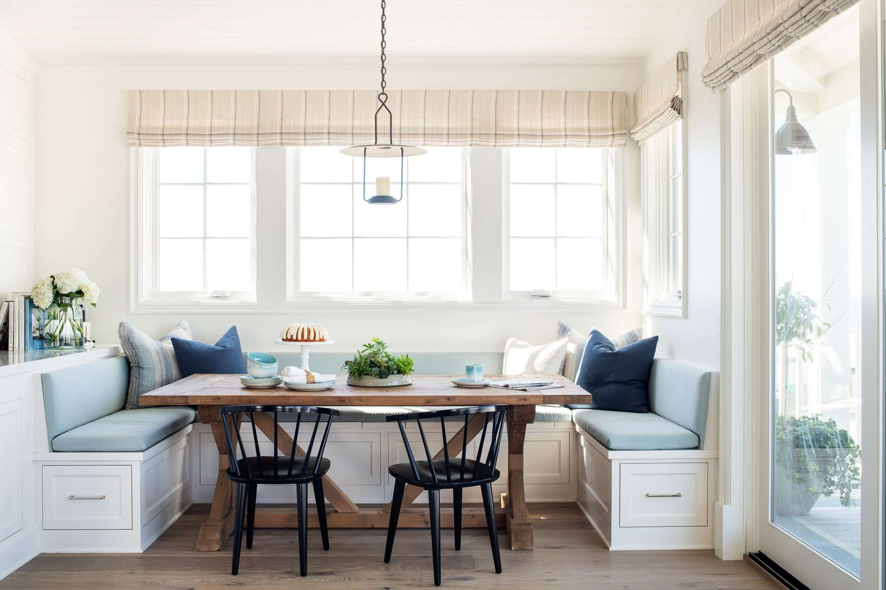 A dining room banquette lined with sky blue cushions and navy throw pillows