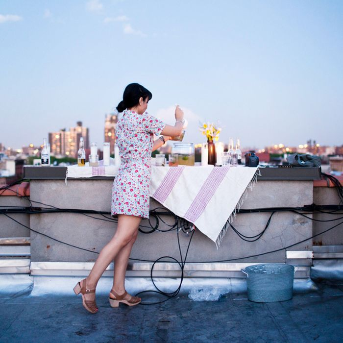 a woman getting a drink at a rooftop bar