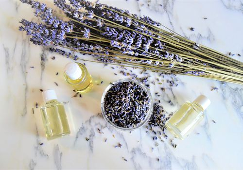 Aromatic oils with lavender flowers on marble background, seen from above