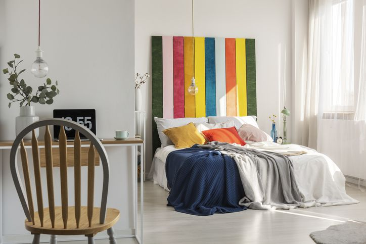 Green, pink, red, orange, yellow and blue bedhead behind king size bed with pillows and blankets