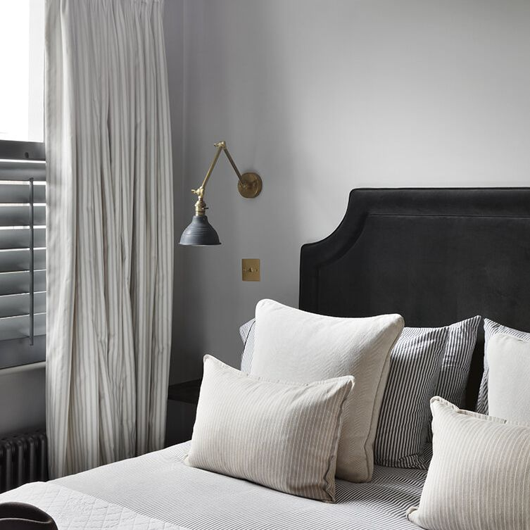 A bedroom with light gray walls