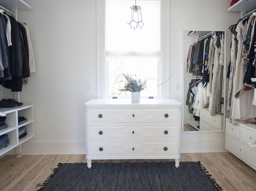 Bedroom turned closet with a white dresser and navy rug