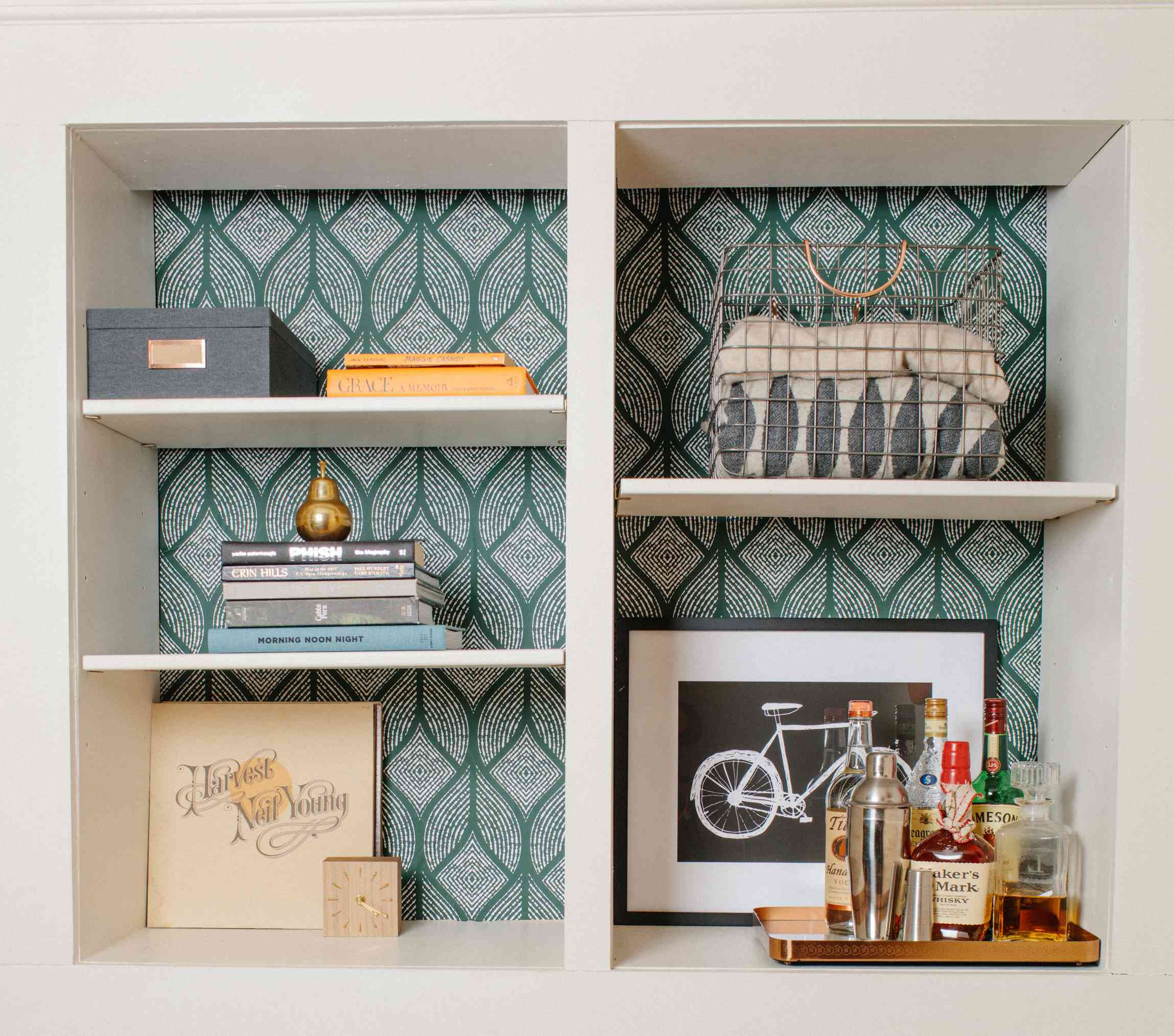 Wallpapered built-in with decorative objects.