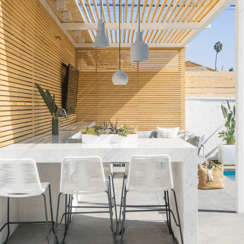 A wood-lined deck with white marble countertops and white pendant lights