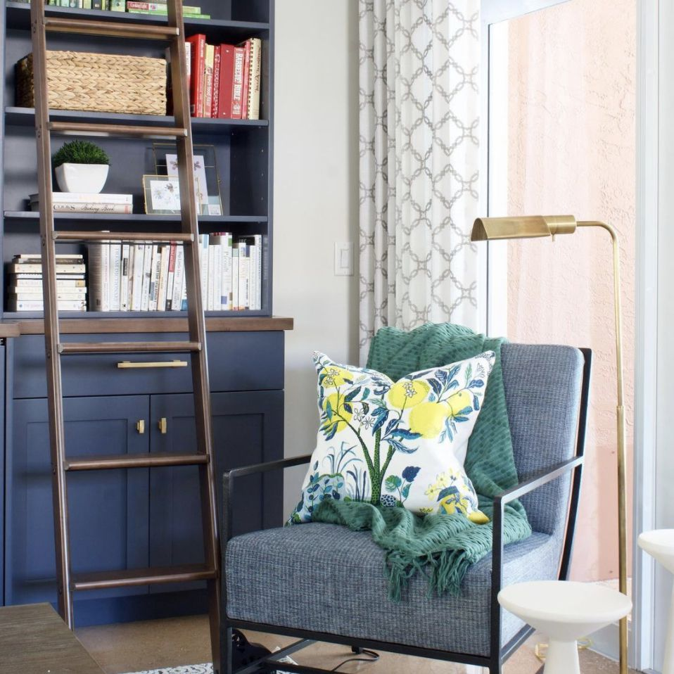 living room with navy blue bookshelf and rolling ladder attached