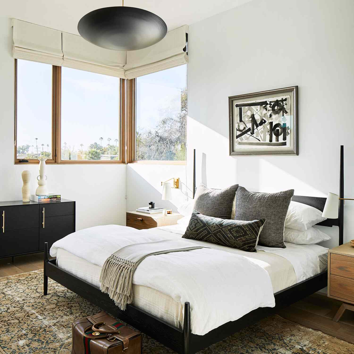 A modern bedroom with a bold black chandelier