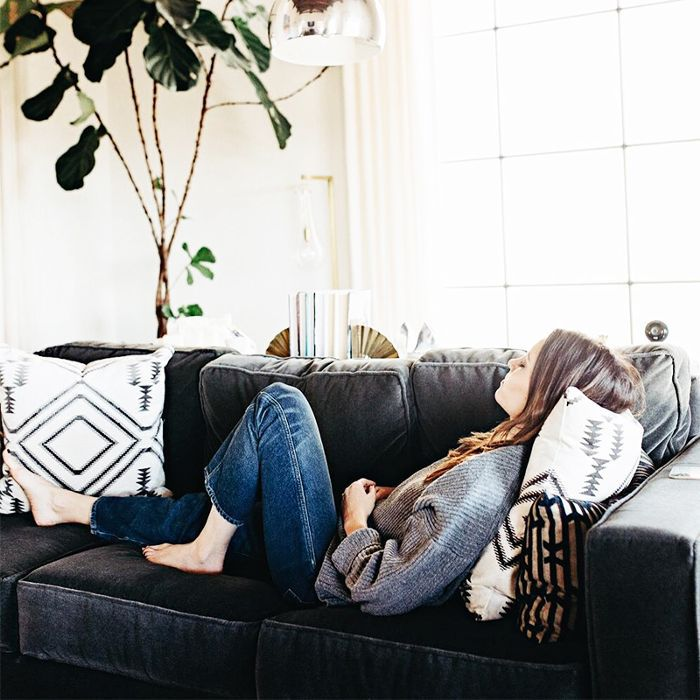a woman practicing mindfulness sitting on a sofa
