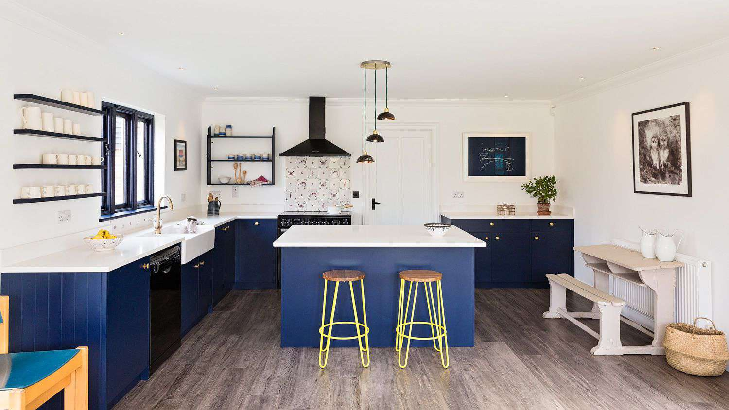 White kitchen with bright blue island and cabinets.