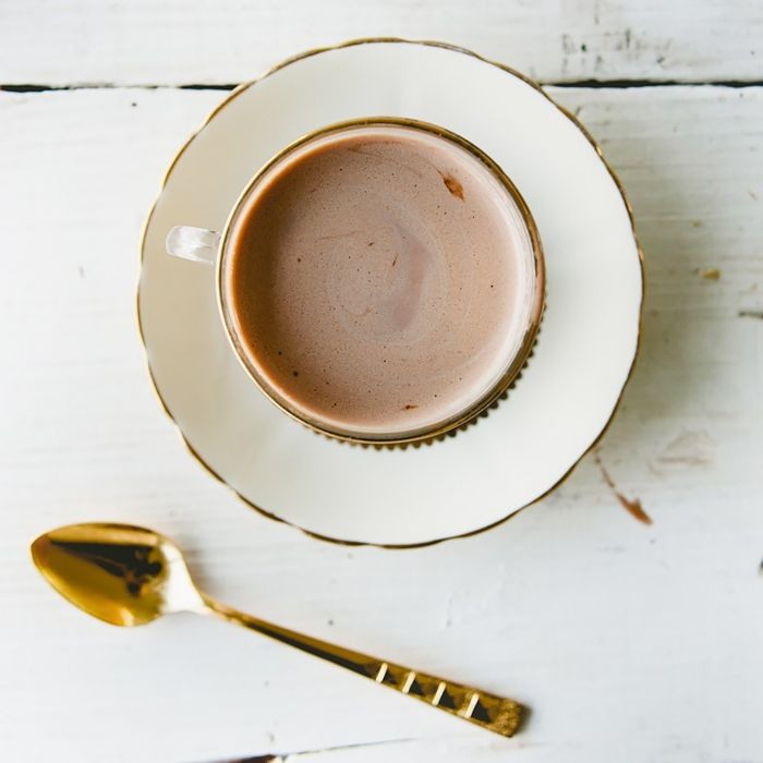 Looking down at a cup full of hot chocolate that's sitting on a saucer. A gold spoon sits on the table.