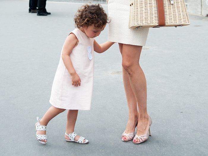 a little girl standing at her mother's legs