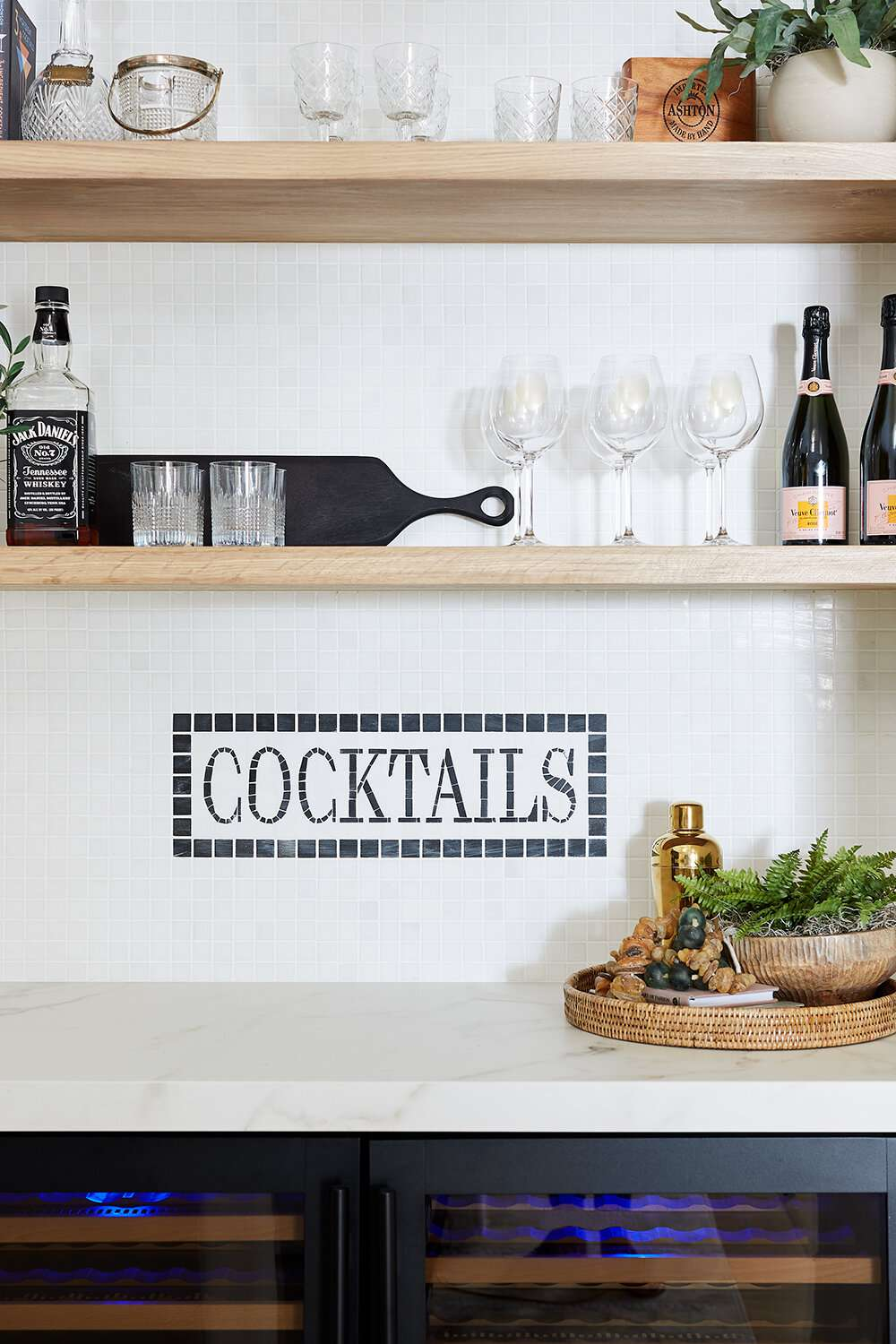 A wet bar backsplash which boasts a mosaic spelling out the word