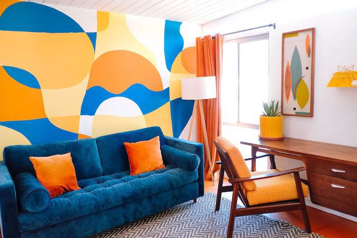 blue, orange, yellow, and white abstract painted wall with blue couch