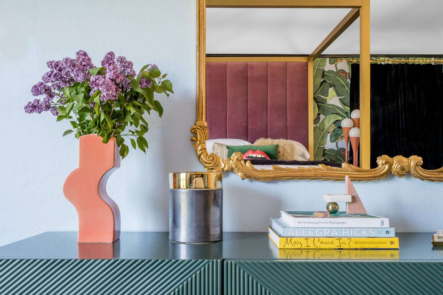 maximalist vignette with coffee table books and a vase