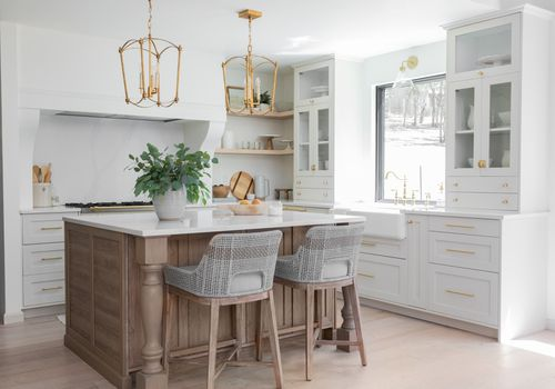 Bright white kitchen with wooden island and gold hardware.